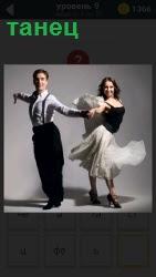 Мужчина и женщина танцуют красивый танец. Девушка в бальном платье и мужчина в брюках и рубашке соединив вместе руки