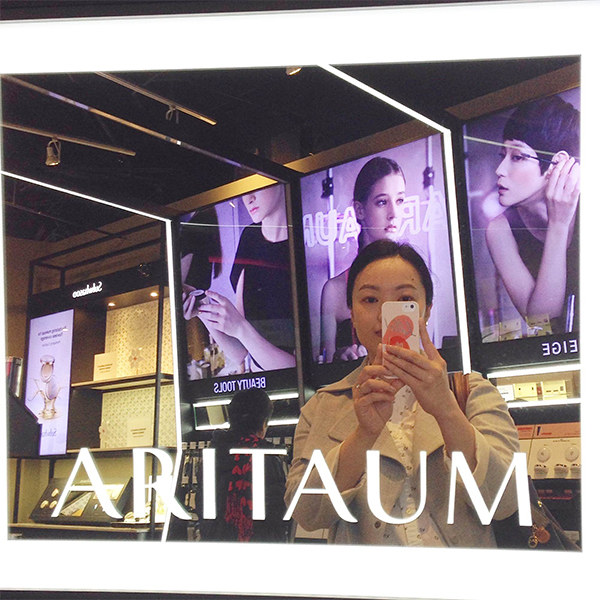 Vancouver blogger Solo Lisa stands in front of a branded Aritaum mirror at a product display and takes a selfie.