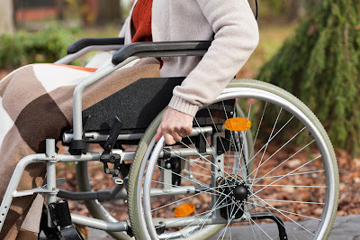 Pic of lady in wheelchair from waist down with focus on her hand on wheel and blanket on her lap
