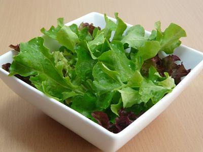 Comer plantas. Hojas de lechuga de dos clases diferentes dentro de un recipiente.