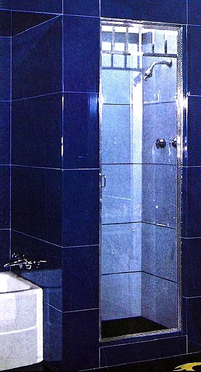 a blue 1946 tiled bathroom shower with glass door