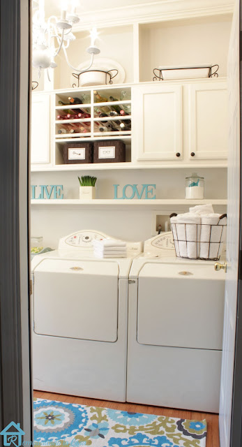 Maytag laundry machines in laundry room with white built-ins and basket of towels