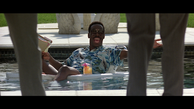eddie murphy excited that his friends have come over to swim with him.