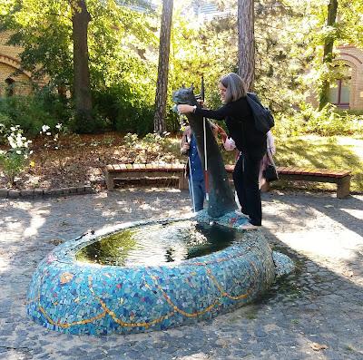 Fotografia da Anja a explorar uma das obras de arte do jarfim, neste caso uma fonte em forma de dragão
