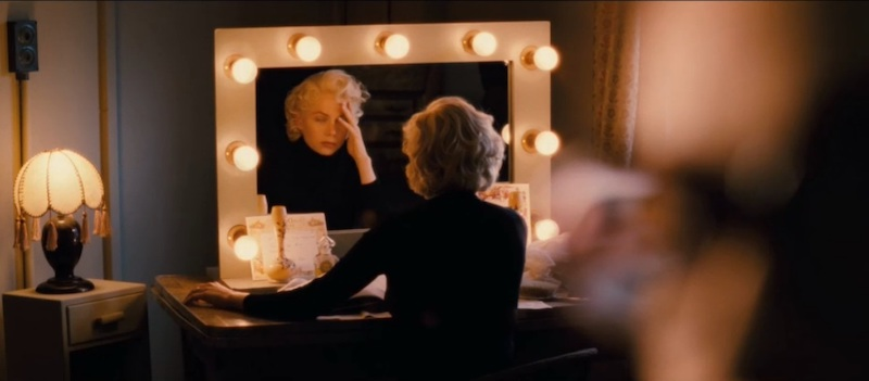 Williams as Marilyn sitting at vanity, its mirror surrounded by bulbs