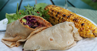 The pulled pork wrap with salad and corn on the cob.