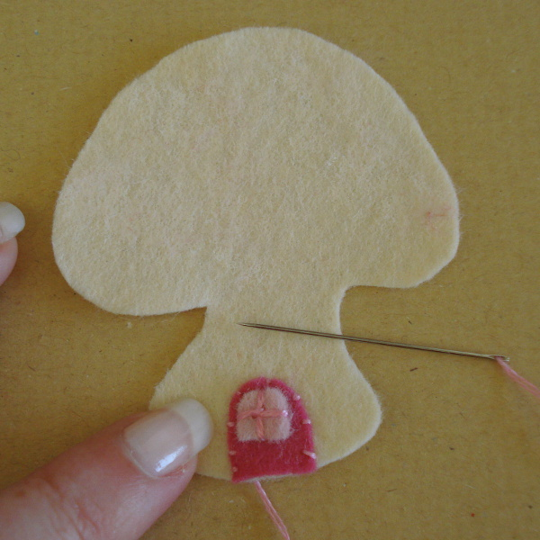 Cream colored felt mushroom toadstool shape with needle and thread sewing on a pink door