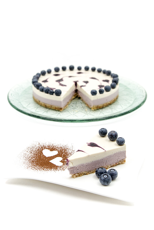 Raw blueberry lime cake on a plate with one piece