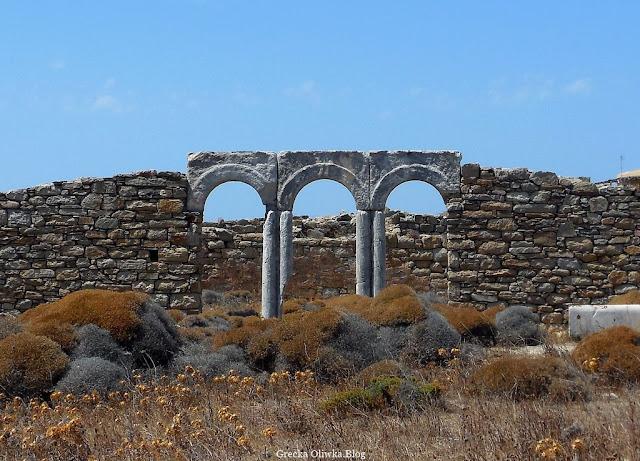 łukowe sklepienie starożytnego greckiego gimnazjonu na tle suchej roślinności i błękitnego nieba Delos Grecja