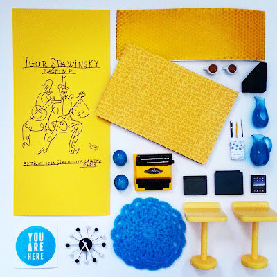 Flat lay of various items in yellow, black and white, mainly in one-twelfth scale miniature.