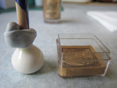White dolls' house miniature vase, with the end of a paint brush blue tacked into it, on a piece of baking paper next to a small plastic container half-filled with gold nail varnish.
