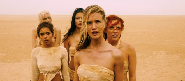 A group of women in the desert dressed in rags.