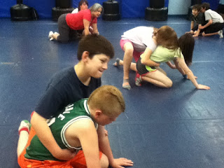 Sports camp students wrestling on mats.