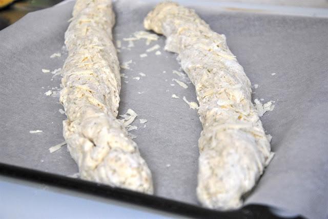 Baguetteteiglinge mit Parmesan bestreuen