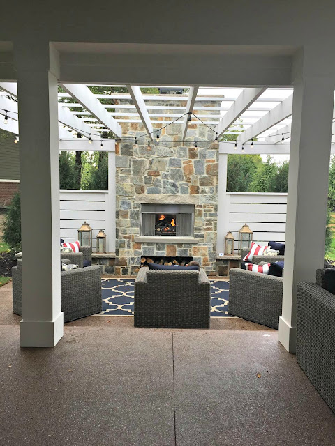 white pergola with fireplace and lights
