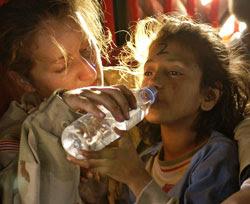 Foto de una asistente humanitaria atendiendo a una niña