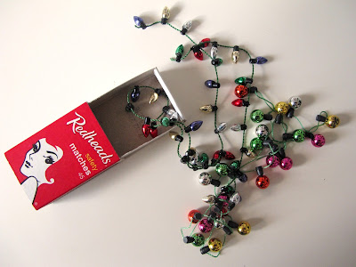 Matchbox with two strings of miniature Christmas lights spilling out of it.