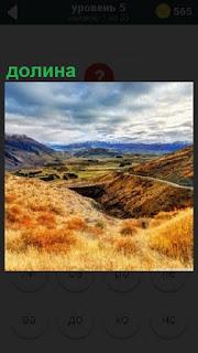 Между холмами протянулась дорога в долине и растет желтая трава