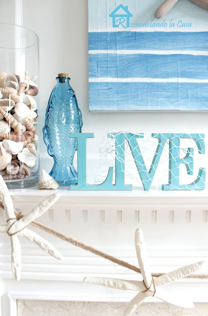 coastal mantel with sea shells, glass fish and blue tones