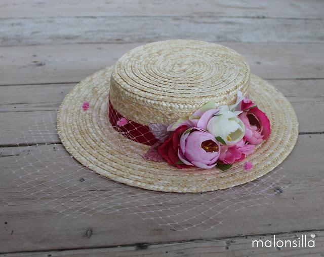 Canotier con flores rosas sobre suelo de madera antguo