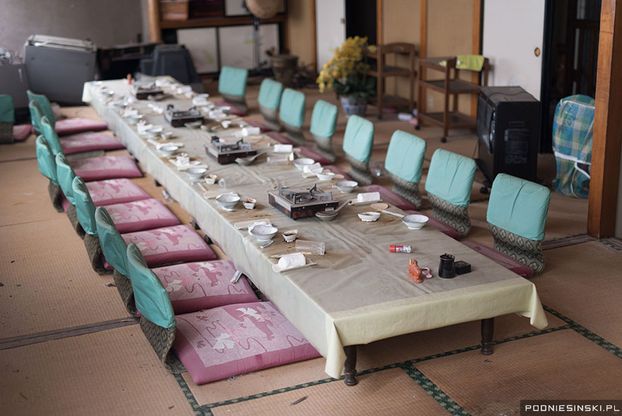 A dining table with portable cookers ready to prepare food looks like it was left in haste - Never-Before-Seen Images Reveal How The Fukushima Exclusion Zone Was Swallowed By Nature