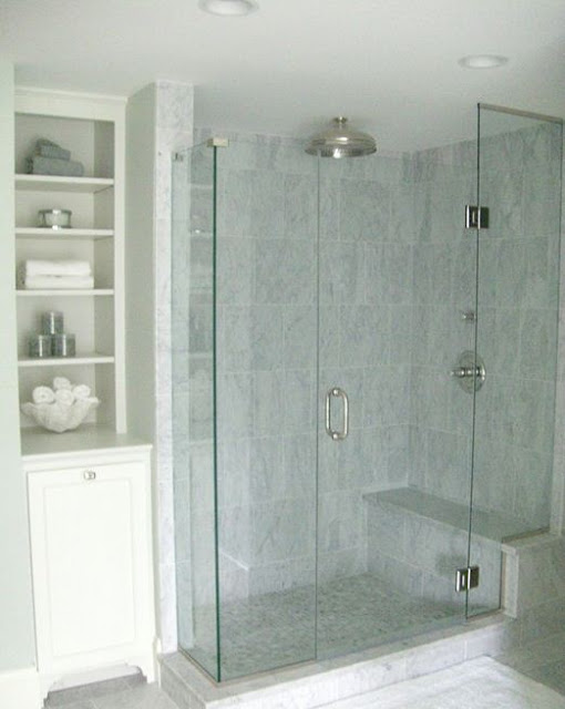 small bath design with storage and glass shower with marble