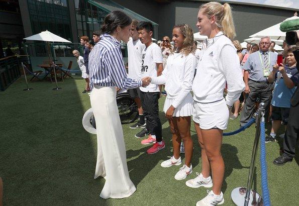 Kate Middleton wore a bespoke Jenny Packham dress. Meghan Markle wore Ralph Lauren Striped Cotton Shirt and Charmain Silk Wide leg Pant