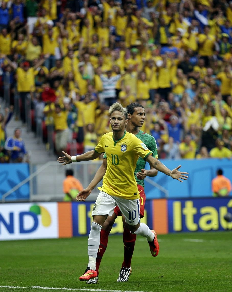 Brazil's Neymar runs past Cameroon's Joel Matip after scoring his side's first goal during the group A World Cup soccer match between Cameroon and Brazil at the Estadio Nacional in Brasilia, Brazil, Monday, June 23, 2014.
