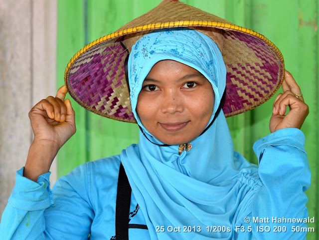 Asian conical hat, conical straw hat, caping, sedge hat, rice hat, paddy hat, young Kalimantan woman, young Muslim woman with conical hat, portrait, headshot, Indonesia, West Kalimantan, Pangkalan Bun