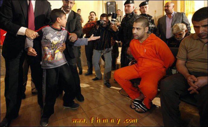 7a161a09a طفل يقف امام قاتـــــــــل ابيه ....اقوى صورة مؤثرة عام 2011