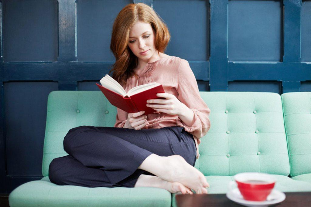 Mujer leyendo sobre sofá