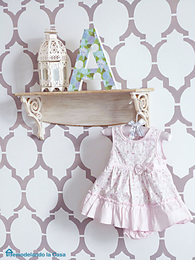 purple nursery with a cute girl's dress as decor on a shelf