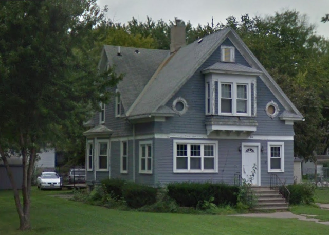 blue grey 1-1/2 story house with enclosed front porch and bay window on the side