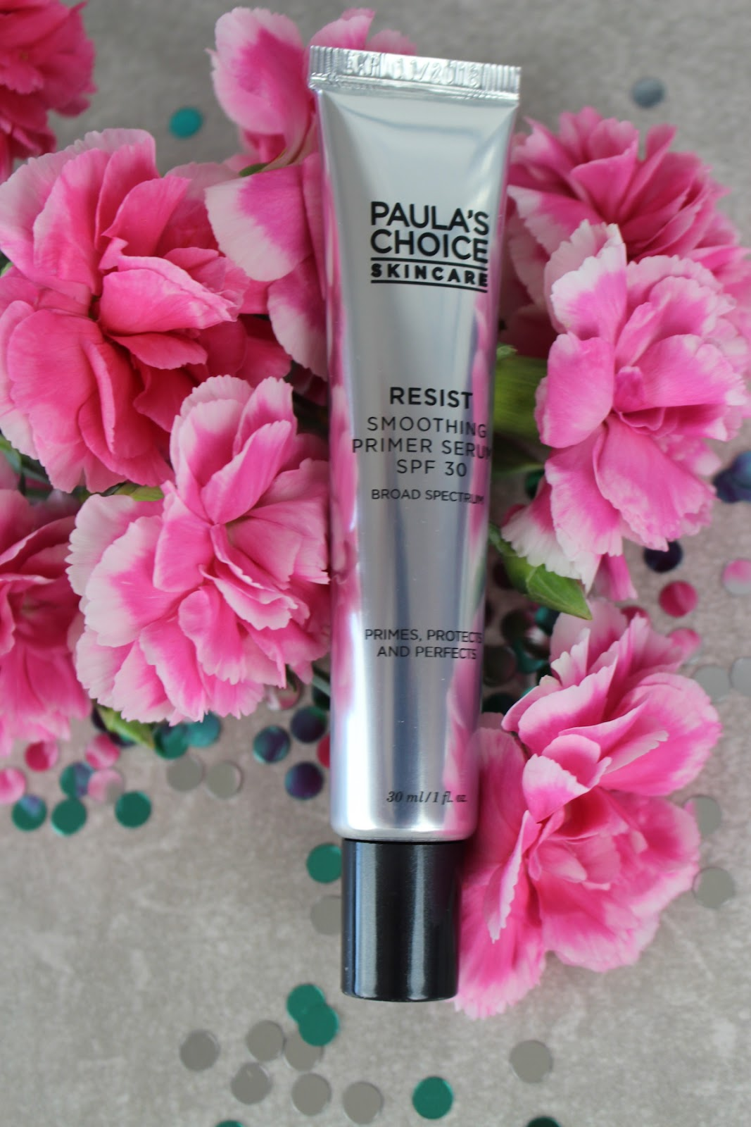 This is a close up of Paula's Choice Smoothing Primer Serum SPF 30, surrounded by beautiful pink flowers.