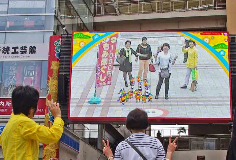 tourists view themselves on big movie screen