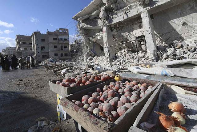 Procura de vítimass em mercadinho arruinado por bombardeio da força aérea da Rússia, em Ariha, província de Idlib.
