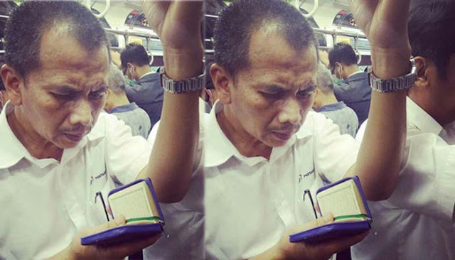Meski Harus Berdiri Dan Penuh Sesak, Bapak Ini Tetap Khusyuk Membaca Al Qur'an