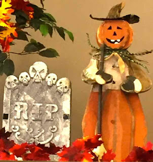 Halloween decorations witj RIP sign and scarecrow.