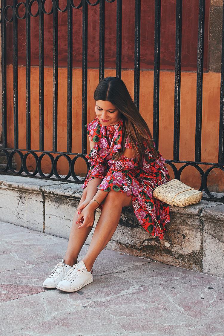 Outfit con vestido de flores, bolso de rafia y zapatillas littleblackcoconut