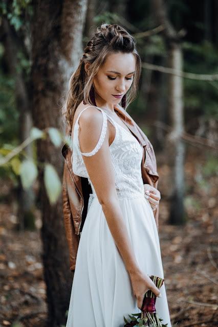 Panna Młoda w boho stylizacji: suknia ślubna Wedding Room Gdynia, skórzana brązowa kurtka, warkocz i bukiet zielono-burgundowy.