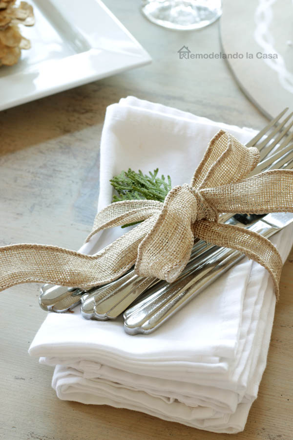 white Napkins and silverware bundled up with burlap ribbon and clippings from the yard.