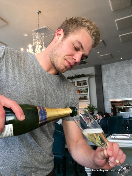 waiter Greg pours sparkling wine at The Dorian in San Francisco, California