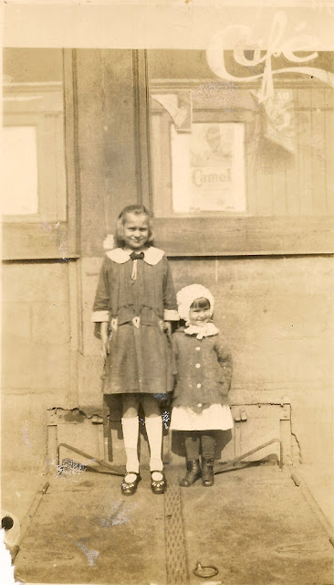 Two girls standing on the basement doors of a cafe.