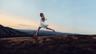 Chica rubia saltando por el césped en una montaña