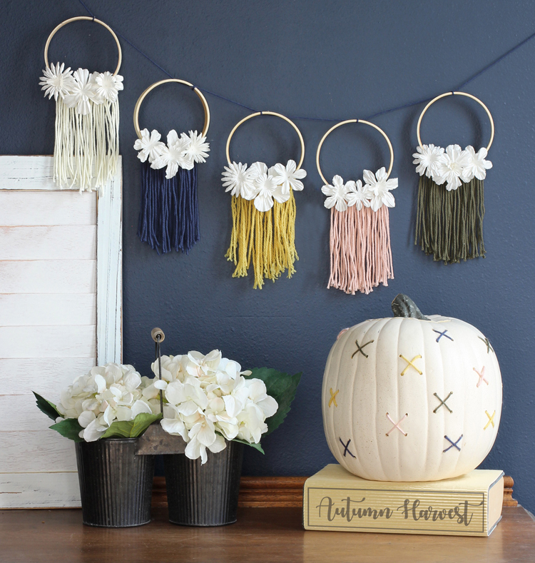 Create your own DIY fall decorations in a nontraditional color scheme: a beautiful macrame inspired mini embroidery hoop banner and a fun cross-stitched pumpkin.