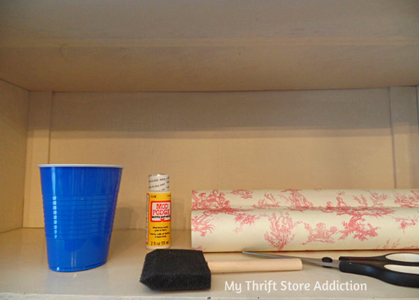 How to Transform Shelves with Thrift Store Paper mythriftstoreaddiction.blogspot.com China cabinet makeover using thrift store draw liners and mod podge.