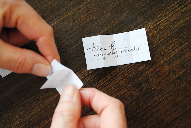 Handen die briefjes met de namen van de winnaars openvouwen