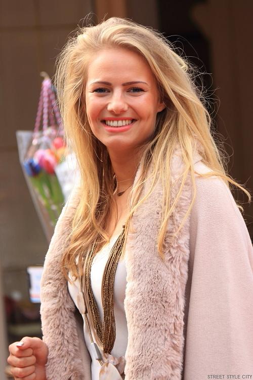Beautiful blond dutch girl wearing winter coat in the street. Streetstyle fashion photography.