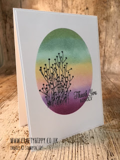 This image shows a handmade card with the silhouette of flowers over a rainbow oval and has been made with the Enjoy Life stamp set from Stampin' Up!