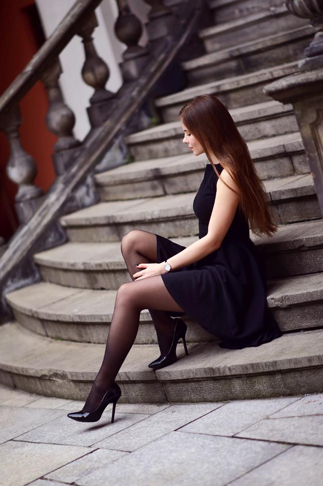 Czarna sukienka z dłuższym tyłem, czarne pończochy oraz lakierowane szpilki